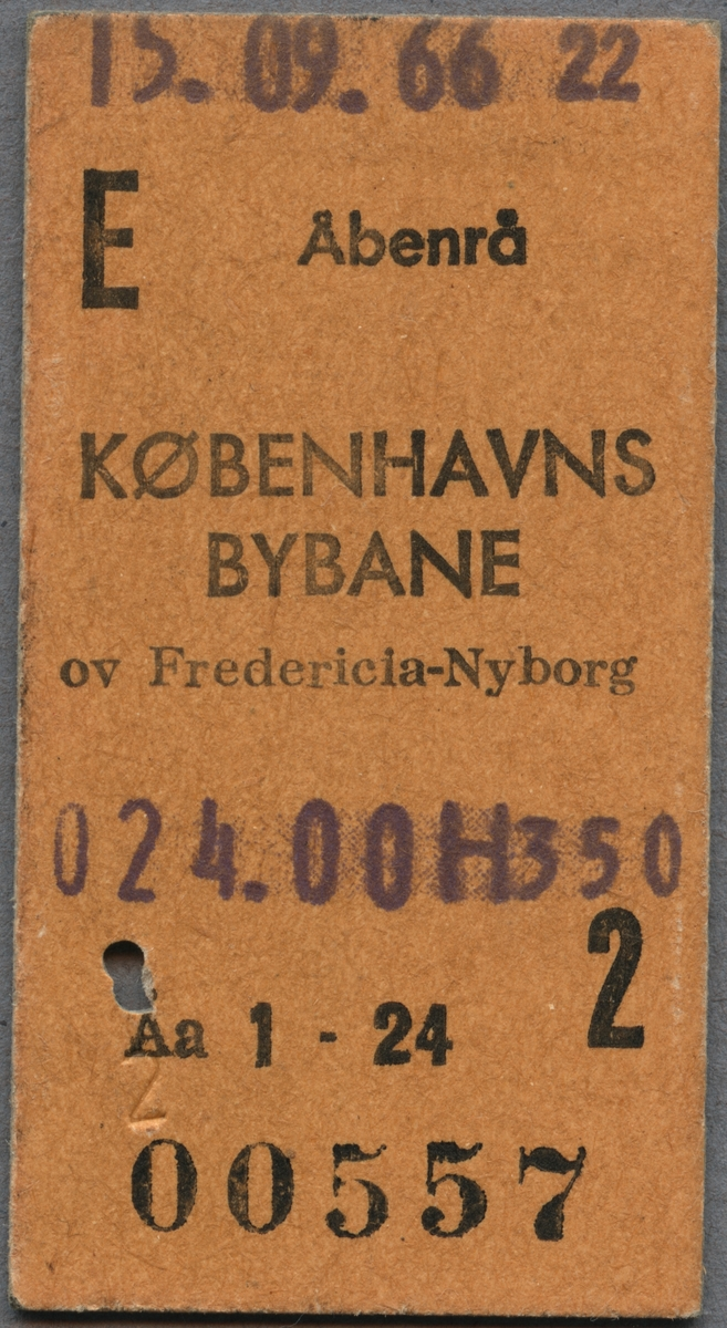 """Edmonsonsk biljett av brun kartong med tryckt svart text: """"E Åbenrå KØBENHAVNS BYBANE ov Fredericia-Nyborg 024.00 2"""".  Biljetten har datumet 15.09.66 stämplat högst upp samt ett hål efter biljettång. När biljettången användes blev också """"2"""" präglat på framsidan intill hålet. Biljettnumret """"00557"""" står i nederkant."""