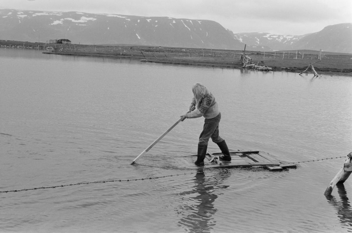 En gutt leker på en flåte i vannet