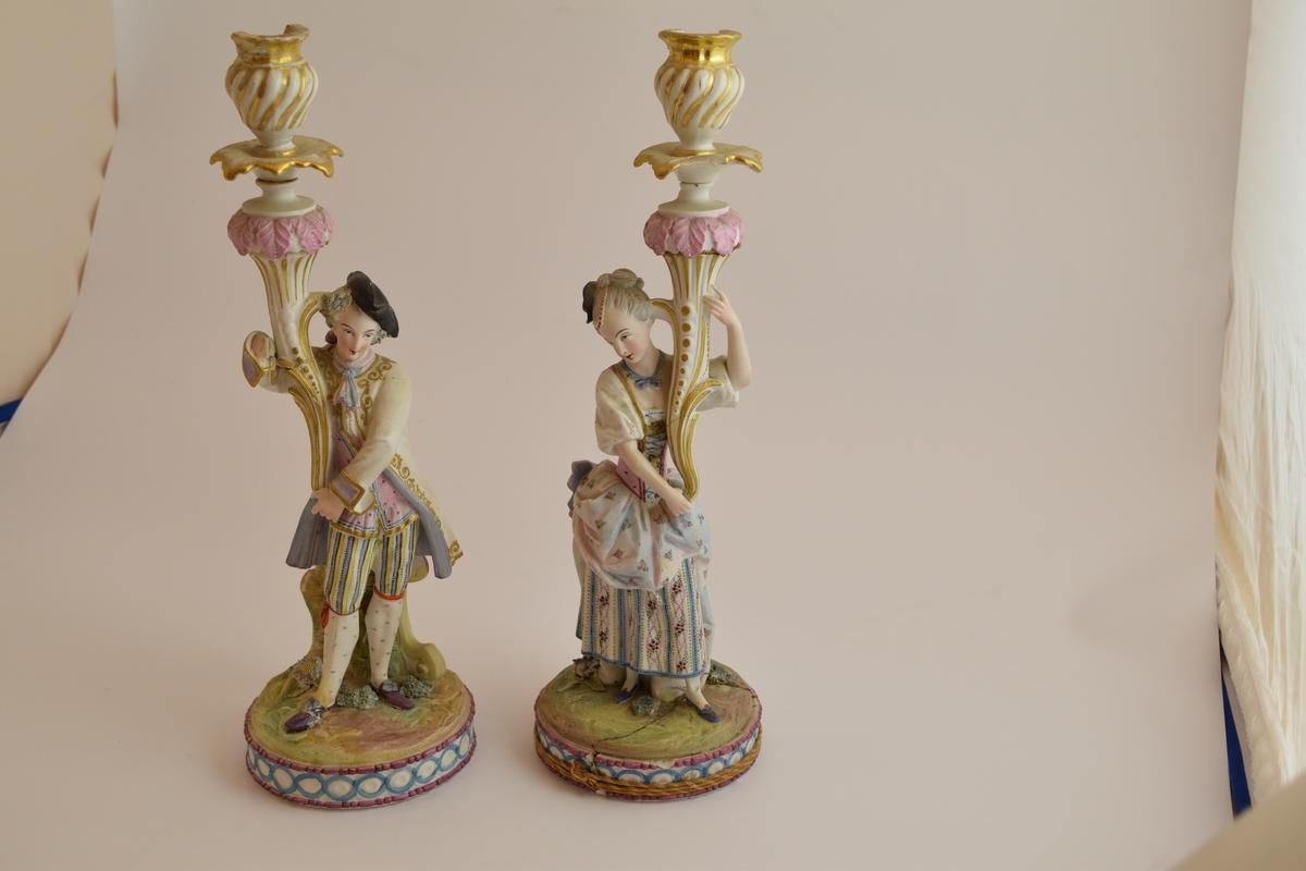 To lysestaker i form av statuetter av en mann og en kvinne i typisk 1700-talls fransk overklasse bekledning, De holder begge hver sin blomst som fungerer som stearinlysholdere.