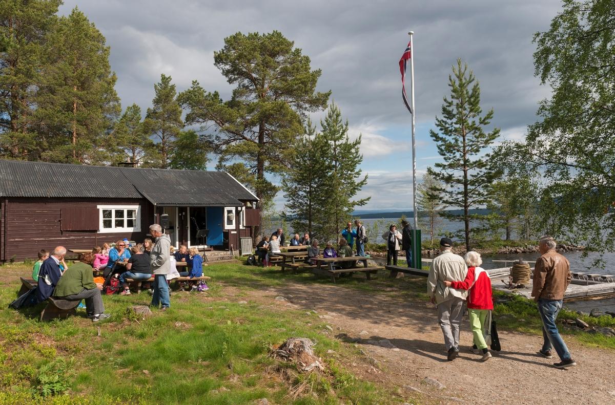 Fra jubileumsarrangementet for slepebåten «Trysilknut» ved Sørlistøa fløtermuseum ved Osensjøen i Åmot 11. juni 2014.  Fotografiet er tatt på sletta foran huset museet bruker som kafé- og resepsjonslokale, men som opprinnelig inneholdt mannskapsrom og kontor for fløtersjefen.  Mange hadde allerede tatt plass på de framsatte benkene da fotografiet ble tatt, andre var på veg inn på området.  Arrangementet samlet drøyt 30 mennesker.  Til høyre i bildet skimter vi en spillflåte av den typen fløterne i Osen brukte for å få tømmeret over sjøen før Christiania Tømmerdirektion fikk bygd den nevnte slepebåten vinteren 1913-1914.  Jubileumsarrangementet samlet drøyt 30 gjester.   Mer informasjon om båten Trysilknut finnes under fanen «Andre opplysninger».