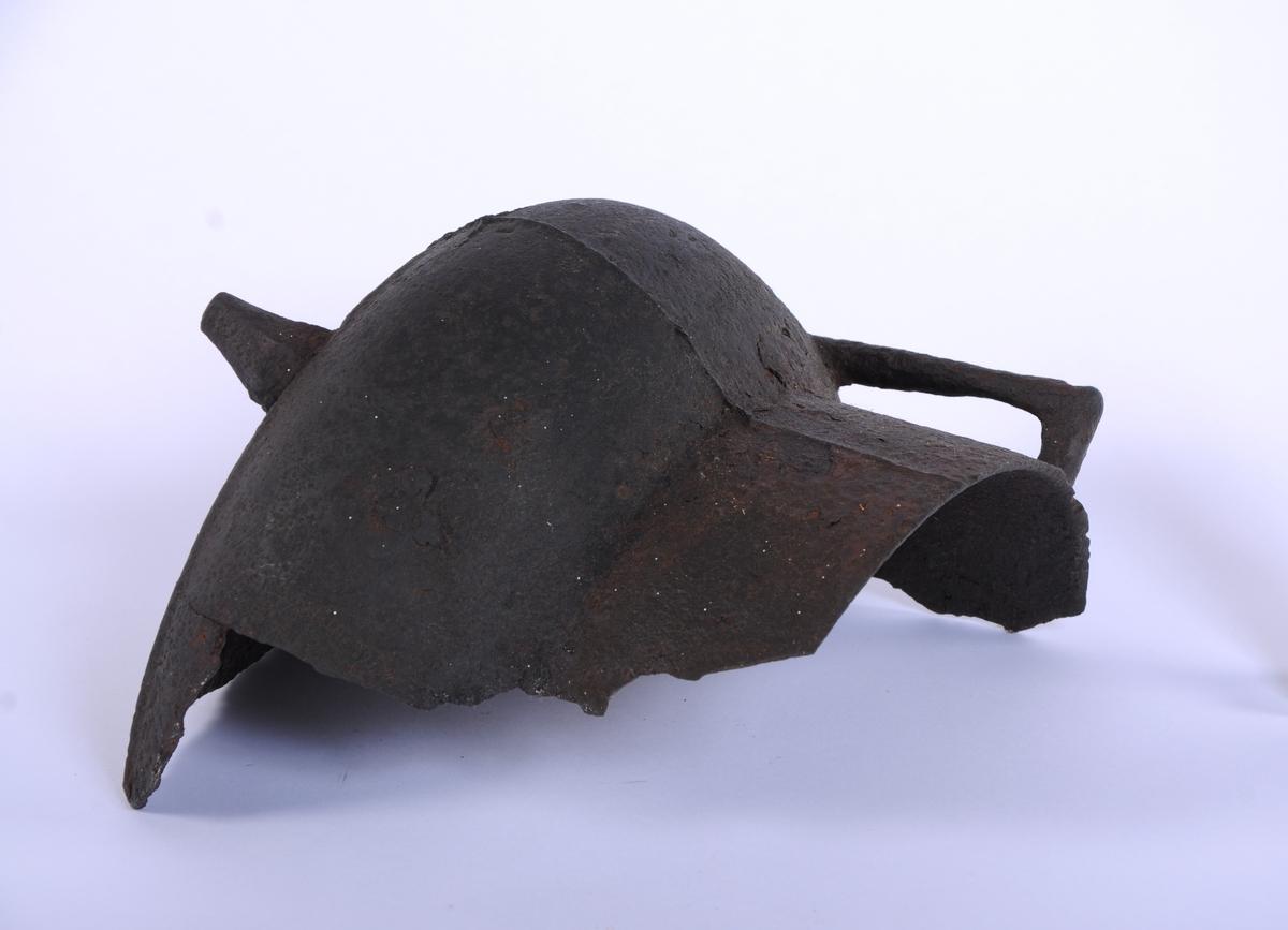 Form: Vid buk, hals skråner utover. Håndtak og to ben. Støpekant er loddrett langs siden.  Jerngryte, halvpart av