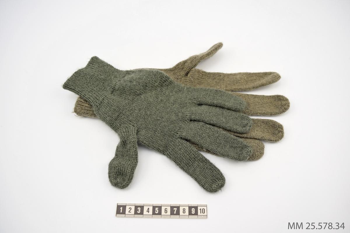 Stickade fingervantar i ylle. Vantarna är gråbruna, den ena något mörkare än den andra. Passar på såväl höger som vänster hand.