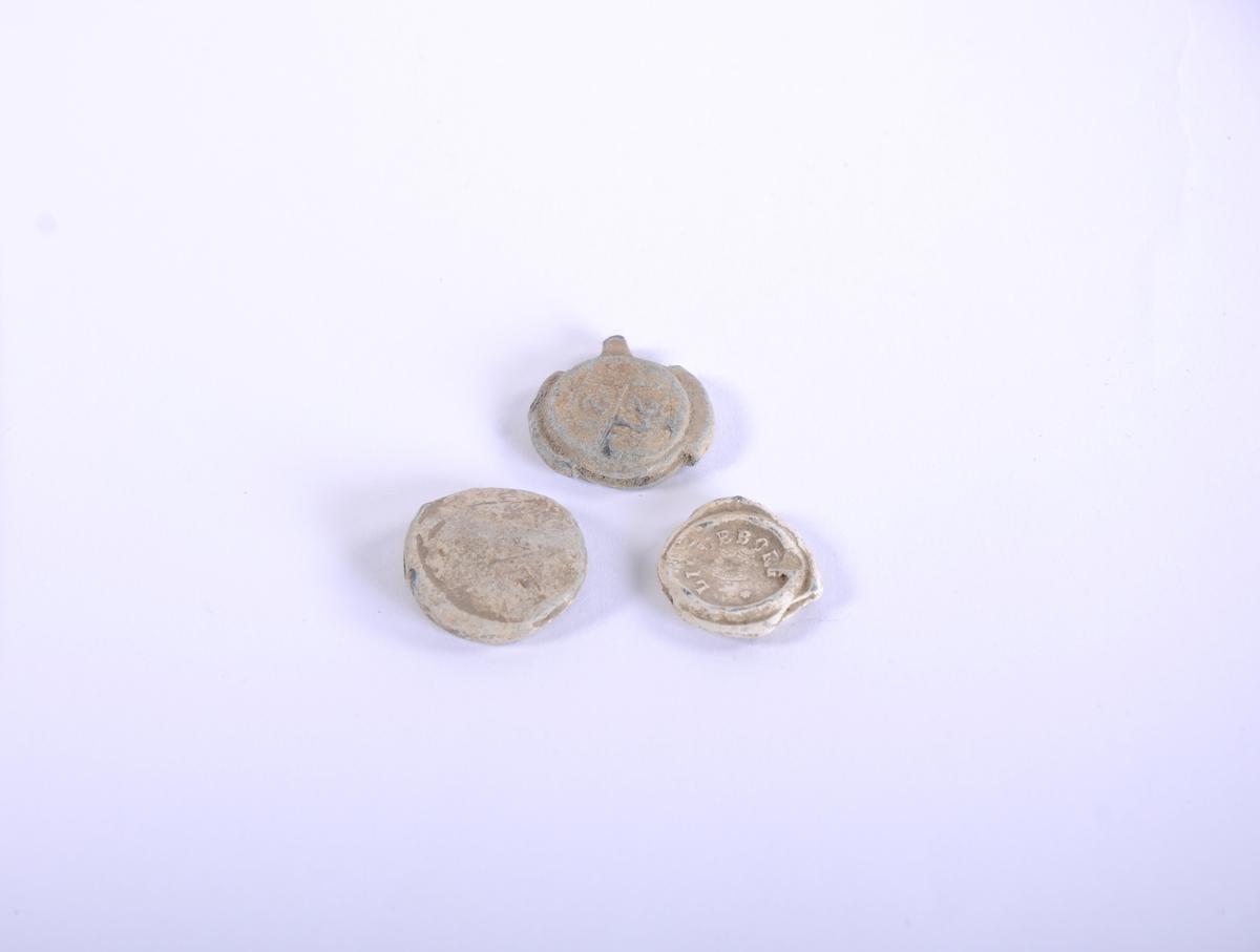 Vareplomber i bly. Vareplombene består av to runde blyplater med en streng imellom og en nagle. Plomben ble festet til tekstilet med en tang og deretter stemplet slik at man kan se hvor varen kom fra. Kalles også tekstilplombe eller sekkeplombe.