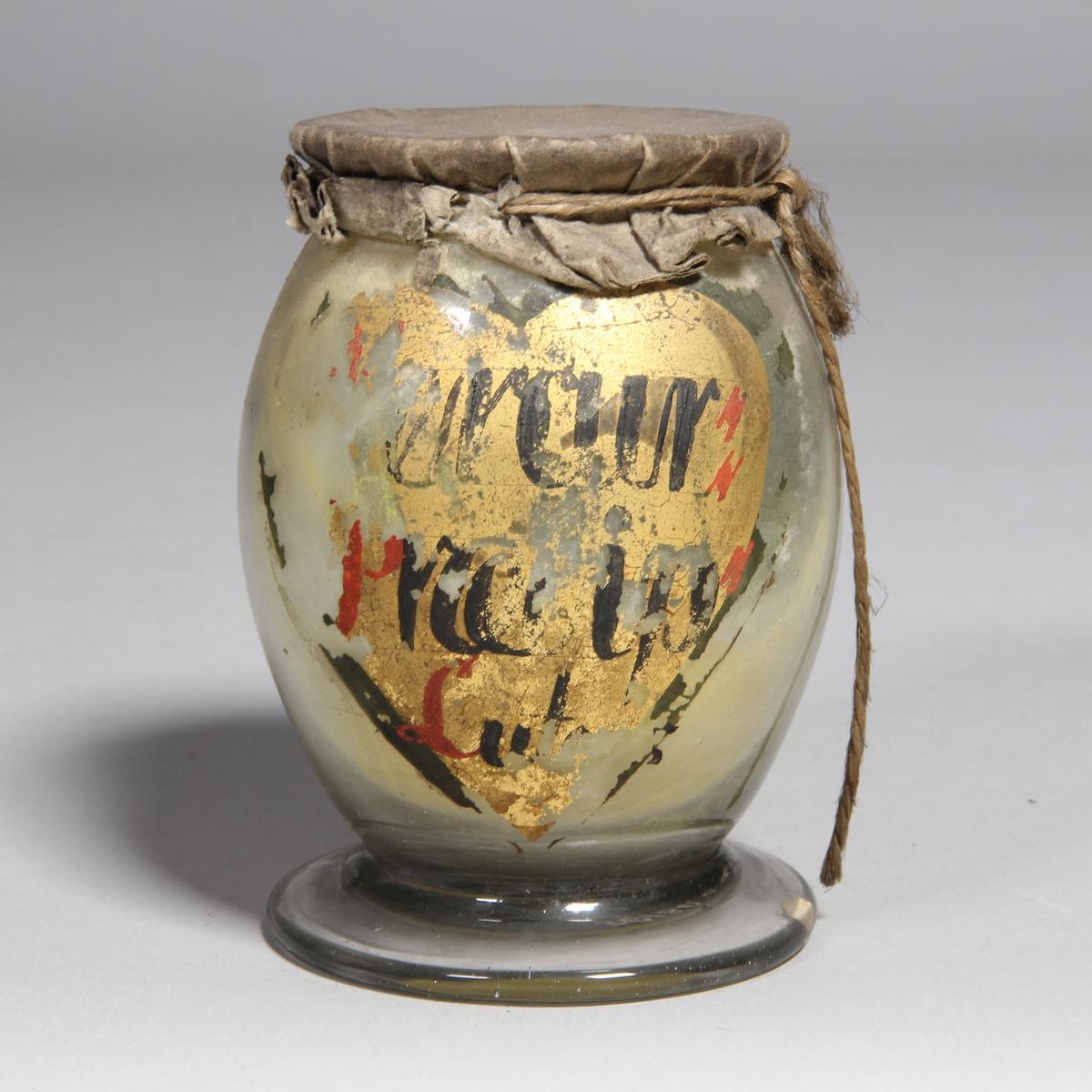 Burk av klart glas. Rundad med utvikt fot, överbundet lock av papper och fäst med snöre. Två målade etiketter, den ena  hjärtformad med text, den andra utan text. Innehåller gult pulver.