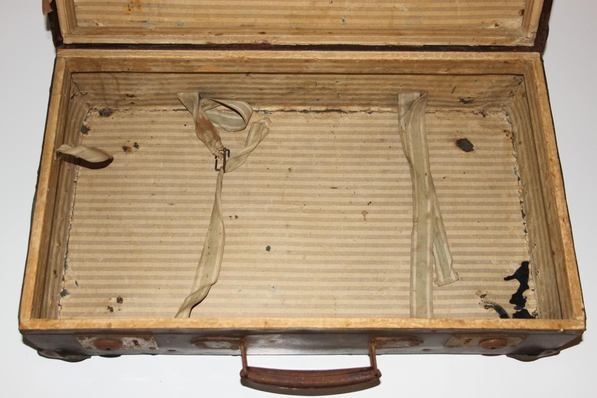 """Brun Koffert med hjørnebeslag i metall. Hengslet. Dobbel lås . Nøkkel mangler. Håndtak i metall.  Meget slitt. Hull i lokk.  Med stropper i tøy. Stripet innvendig foring i papir. Foret har sorte blekkflekker. 4 knappeformede ben i metall på undersiden. Begge sider har limrester etter reisegodsmerking.  En resterende lapp på koffertens venstre side pålydende """" 106 . Fra Fauske til Kristiansand. NSB"""""""