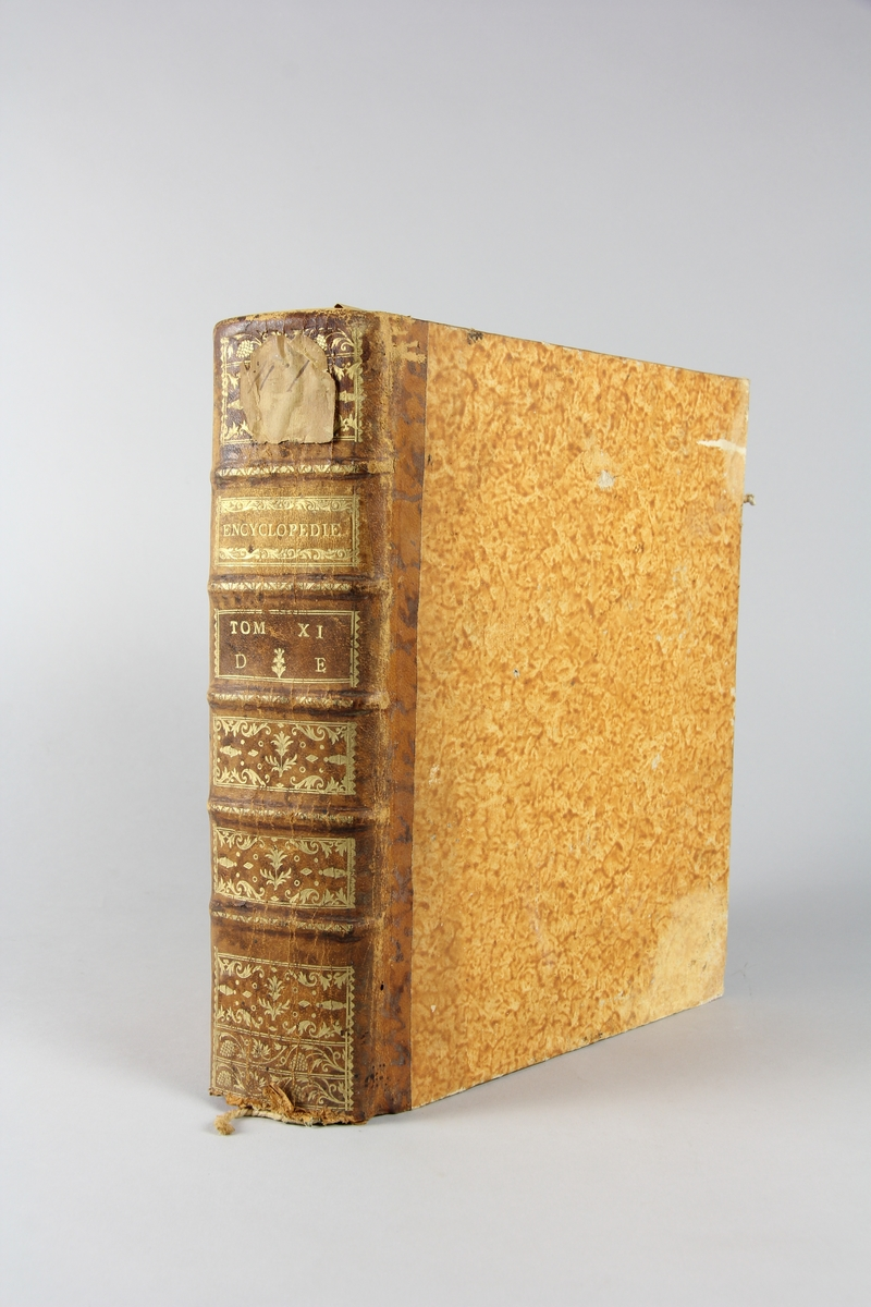 """Bok, """"Encyclopédie ou dictionnaire raisonné des sciences, des arts et des métiers"""" av Diderot och d`Alembert, utgiven 1778. Tredje upplagan, vol. 11. Halvfranskt band med pärmar av papp med påklistrat marmorerat papper, rygg av skinn med fem upphöjda bind med guldpräglad dekor, blindpressad och guldornerad rygg, titelfält med blindpressad titel och ett mörkare fält med volymens nummer. Påklistrad pappersetikett med samlingsnummer med bläck. Med rött snitt. Bokmärke i form av grönt sidenband."""