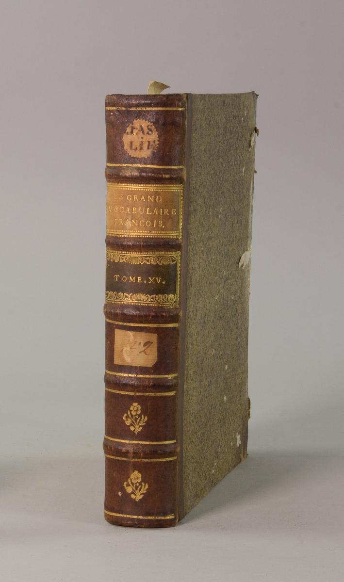"""Bok, halvfranskt band """"Le grand vocabulaire francois"""", del XV, utgiven i Paris 1771. Band med pärmar av papp med påklistrat stänkt papper, hörn och rygg av skinn med fem upphöjda bind med guldpräglad dekor, titelfält med blindpressad titel och ett mörkare fält med volymens nummer. Med stänkt snitt. Påklistrade etiketter märkta med bläck """"No 2"""" och """"JAS LIE""""."""