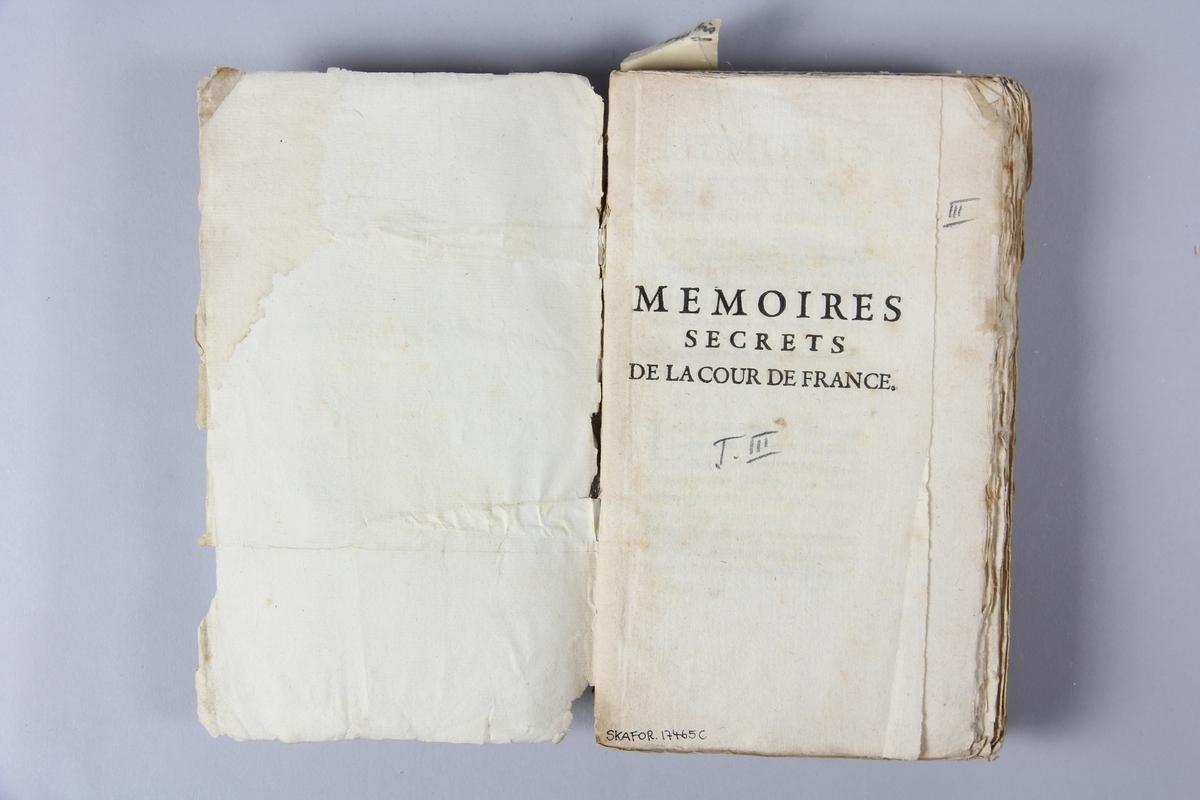 """Bok, häftad, """"Mémoires secrets de la cour de France"""", del 3, tryckt 1733 i Amsterdam. Pärm av marmorerat papper, oskuret snitt. Blekt rygg med etikett med titel och samlingsnummer."""