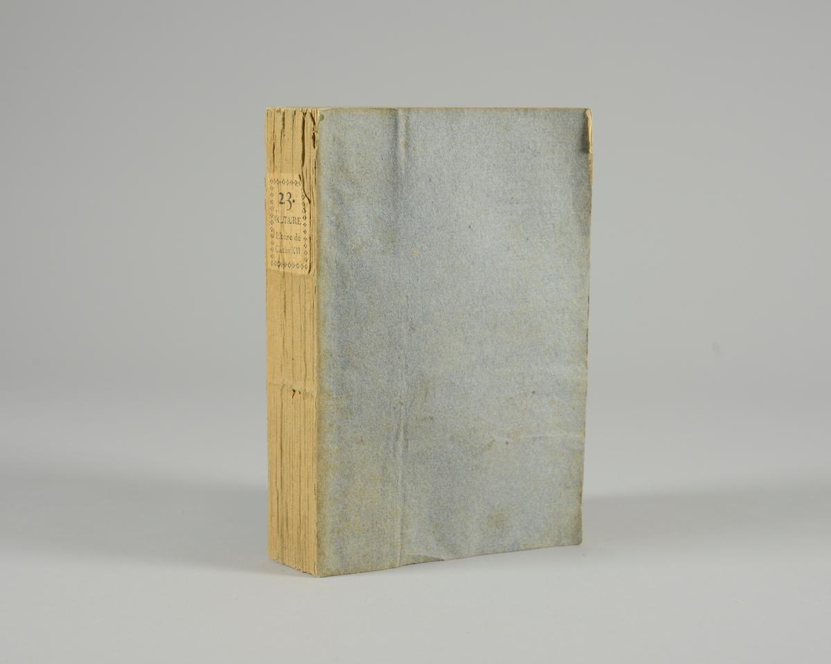 """Bok, pappband,""""Oeuvres completes de Voltaire"""", del 23 Histoire de Charles XII, tryckt 1785. Pärmen klädd med gråblått papper, på pärmens baksida klistrad sida ur annan bok. Med skurna snitt. På ryggen klistrad pappersetikett med tryckt text samt volymens nummer. Ryggen blekt."""