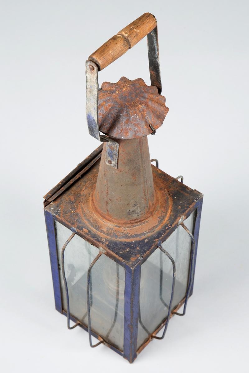 Rektangulær lykt med sylindrisk topp. Glass på fire sider. Brukt til belysning i uthus.  Tilstand: Noe rusten, sprekk i ene glasset, ellers god.