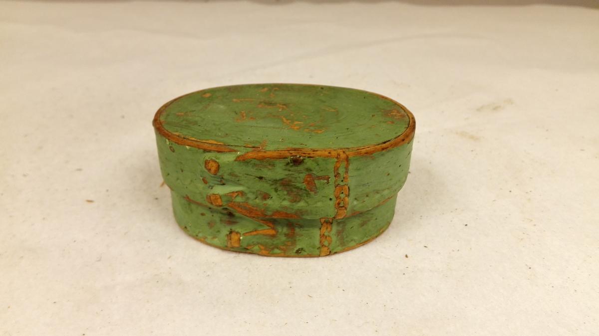 Form: Oval. 1 æske.  Liten oval æske med laag. Bunden 7,3 x 4,9 cm. Trysken og længste siden svöigd og sammenbundet med viertæger. Utvendig grönmalt.  Under bunden indskaaret ANG SDL 1773.  Gave fra smed G.A.Loven, Kaupanger.