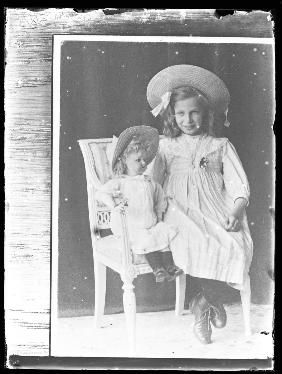 Reprofotografi på beställning av fru Lenander (tolkat som Anna Lenander). Bilden är ett porträtt av en flicka i ljus klänning och halmhatt som sitter på en stol tillsammans med en porslinsdocka.