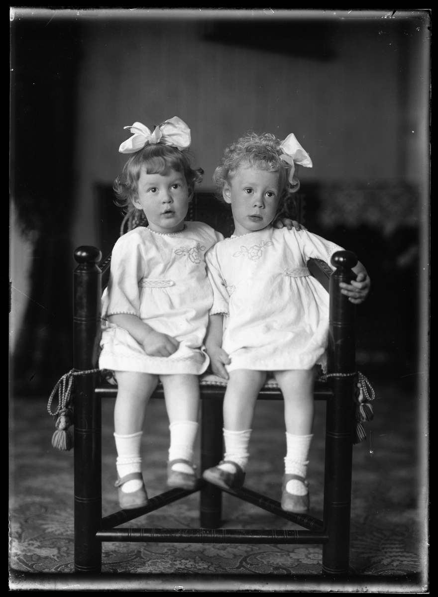 Syskonen Ester och Birgit Tollstadius, klädda i vitt med rosett i håret.