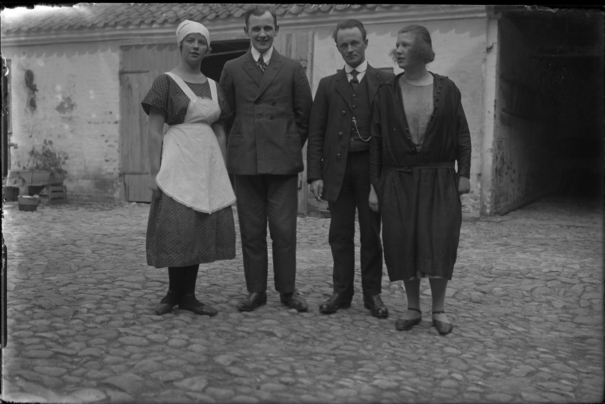Två kvinnor står på en kullerstensklädd innergård, emellan dem står två kostymklädda män. I fotografens egna anteckningar står: Danmarksresan, Anna Hansén med kamrater.