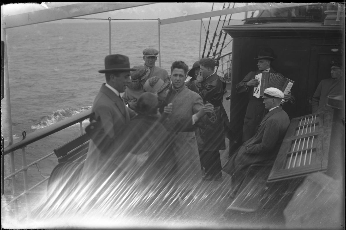Fyra par dansar på ett fartygsdäck medan en man i studentmössa sitter bredvid och en annan man spelar dragspel. I fotografens egna anteckningar står: Danmarksresan, Dans på däck.