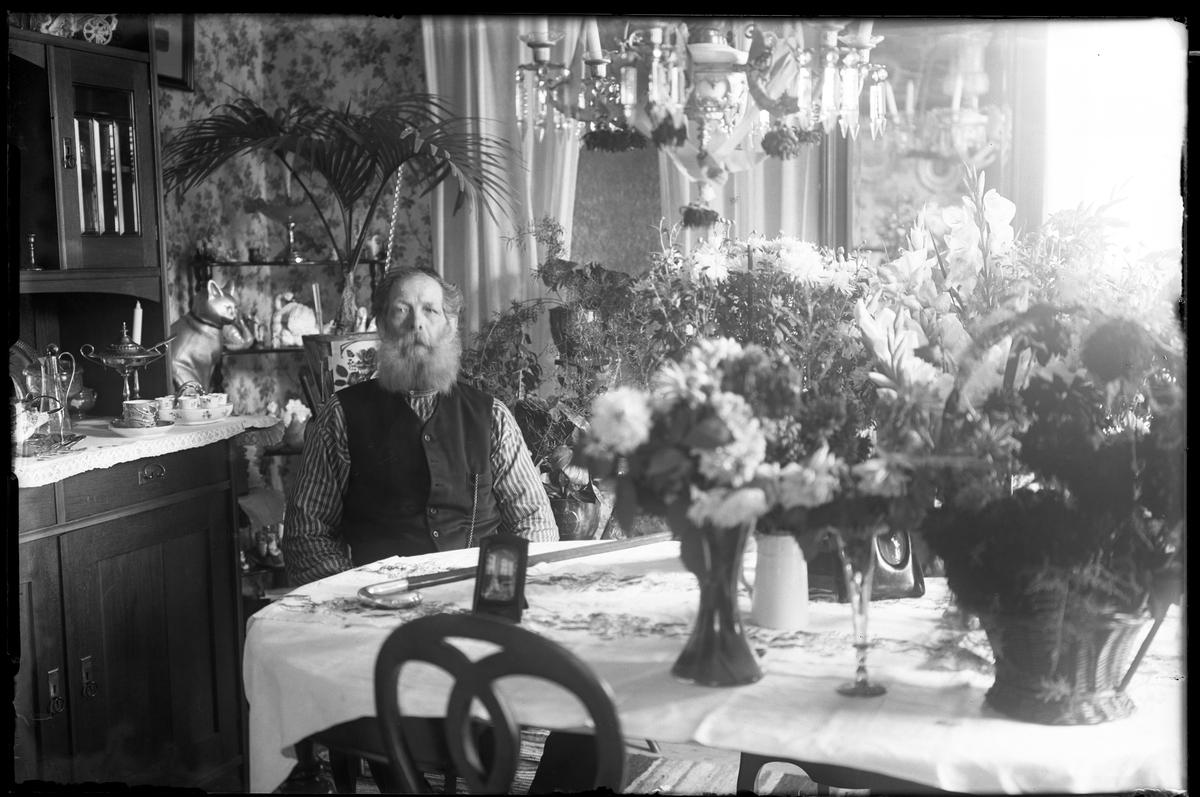 """En man i randig skjorta och väst sitter vid ett bord fullt av blommor. I fotografens egna anteckningar står det """"Lycke 75 år"""""""