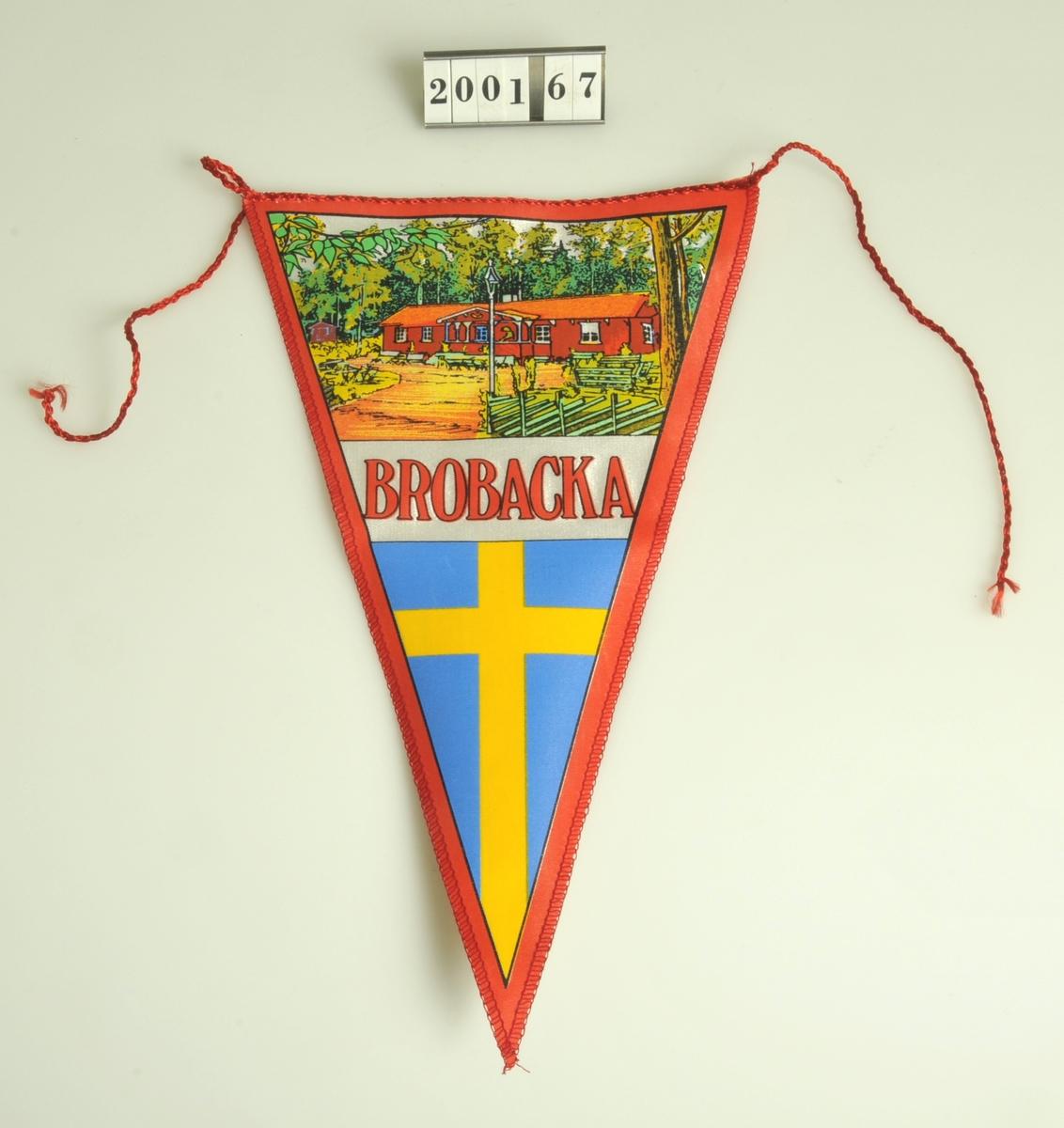 """Triangelformad med sydda kanter i rött som i den övre delen avslutas med två tampar.  I den övre breda delen föreställer trycket Brobacka kaffestuga, under bilden står det """"Brobacka"""" i rött på vit botten. Den nedre spetsiga delen pryda av den svenska flaggan. På baksidan står skrivet med bläck 10:-.  Vimpeln är plastbehandlad.    Bengtsgården, Bälinge."""