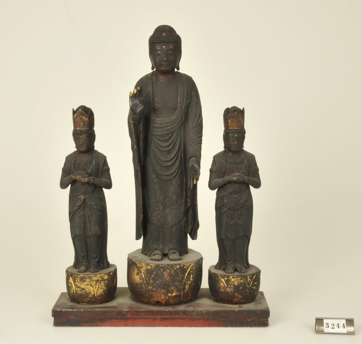 Budda omgiven av två bodhisattvas. Tre personer - en större och två mindre sammonterade. Svartmålade och förgyllda. Höjd: 290 resp 450 mm.   Adelsköldska samlingarna.