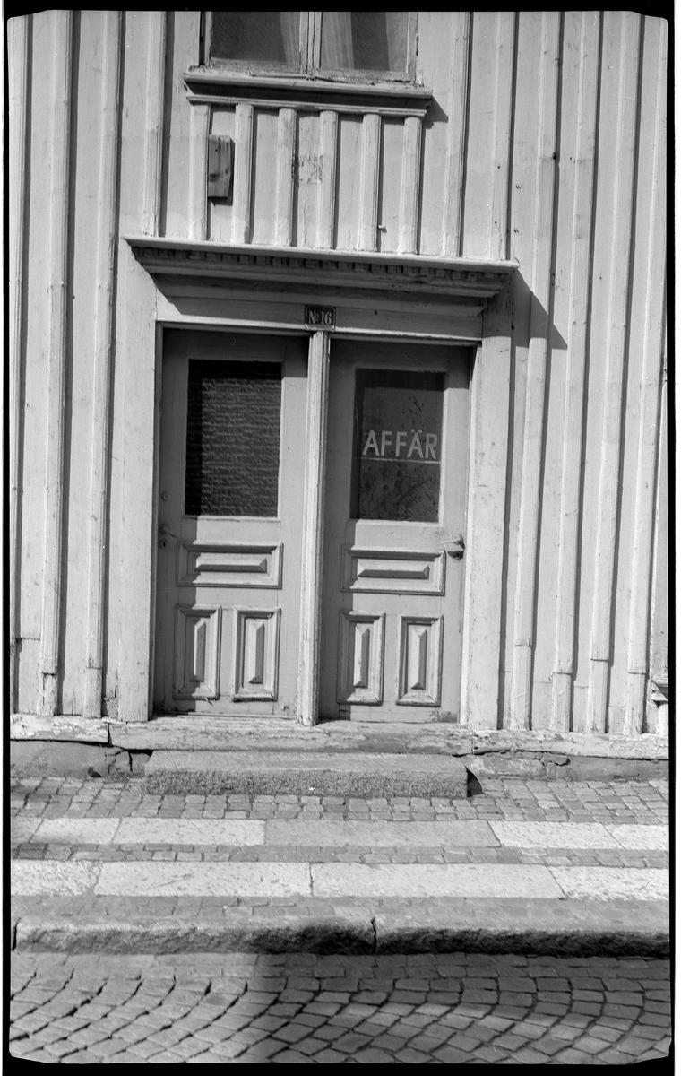 Dörrinfattning på byggnad, Drottninggatan 16, kv Liljan 4.  I dörromfattningen sitter två ytterdörrar, båda identiska med fönster på övre halvan och välarbetad nedre del med tre speglar. En dörr vänsterhängd, en annan högerhängd. På fönsterglaset på dörren till höger står det AFFÄR med versaler och ett streck under ordet.  Krönet på omfattningen är väl dekorerat.  En emaljerad skylt med 'Nr 16' på är centrerad över dörrarna.  En bit upp på väggen syns nedre delen av ett fönster, tvåluft.  Väggen har lockpanel.  Framför dörrarna ligger ett trappsteg av sten.  Trottoaren är belagd med gatsten och två parallella band av kalksten.  En trottoarkant av huggen granit och gata belagd med gatsten i bågformat mönster.  Huset är rivet. Det var förmodligen från tidigt 1800-tal.  foto 9.6.1990