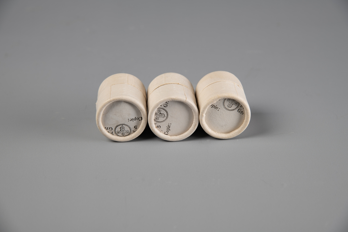 Tre like runde esker av papp. Overfallende lokk. Lokket og bunnen er omtrent like store, lokket kan tas helt av. Pålimt lyserosa papir på lokket. Brukt til piller og dosert pulver på apotek.