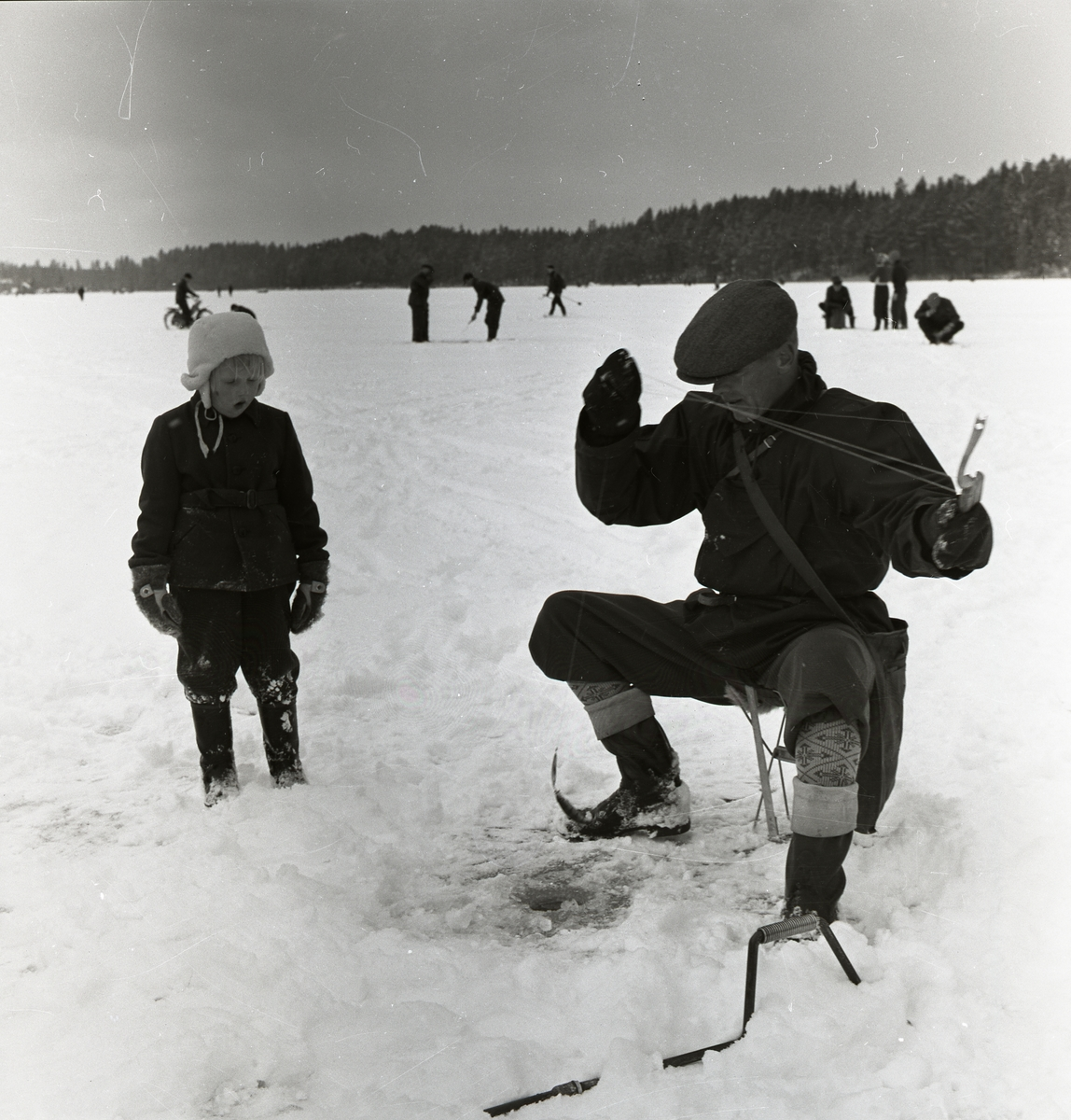 En man sitter vid ett pimpelhål och drar upp en fisk. Ett barn står bredvid och tittar på. IOGT och FK pimpeltävling på Skidtjärn 14 april 1957.