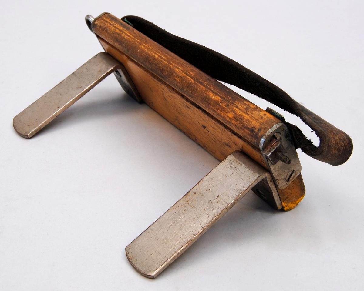 Trälåda av fernissad ek med plåtskodda hörn i svart. På lockets ovansida sitter ett bygelhandtag av mässing och runt lådan finns en läderrem som är fäst på under- och översidan. På lådans framsida finns två låshakar i mässing. På lådans insida finns i botten en fastskruvad avskiljningsbalk och i bortre högra hörnet ett fack för kritor. I främre vänstra insidan finns en hållare för förlängsningsstål och i samma hörn ett fack för trådryttare. På lockets insida finns till vänster tillverkarens logotyp och i mitten en innehållsförteckning på fernissad kartong. (:1)  Trådhållare, två stycken, av björk med beslag av förnicklad mässing. På ovansidan finns ett infällt dosvattenpass och ett handtag av läder. Trådfästet ligger i ett spår på trådhållarens ena kant samt är gängad i ena änden och fäst med fyrkantsmutter. Den ena trådhållarens trådfäste är en aning längre. (:2-3)  Mätsticka, troligen av päronträ, fernissad med tvärslå av mässing. På ena sidan mm-skala och på andra dubbel-mm (som användes vid små kurvradier). På vardera sidan finns ett dosvattenpass infällt. (:4)  Förlängningsplåt till mätstickan av förnicklad mässing. Användes vid små kurvradier. (:5)  Trådrulle av fernissad ek. Trumman är av bleckplåt på stomme av rundträpinnar. Pinnarna är fästa med mässingsspik i trummans sarger och en av pinnarna är förlängd för att fungera som vevhandtag. På ena sargen finns en ståltrådsbygel att fästa trådens karbinhakar i. Handtaget är fäst med träskruv genom en stor bleckplåtsbricka. På trådrullen sitter en 20 m lång mätlina av 1,1 mm, 40-trådig ståltrådskabel med en karbinhake av förnicklad mässing i vardera ändan. (:6)  Mätlina, en extra av samma typ som sitter på trådrullen. 20 m lång av 1,1 mm 40-trådig ståltrådskabel med karbinhakar av förnicklad mässing i ändarna. (:7)  Fettkritor, gula av märket Helsingborg Bosco. Omslaget är gult med röda och gröna färgfält samt med en svart oval där varumärkesnamnet står. Fyra kritor relativt hela samt fyra stumpar. (:8-11)  Tråd