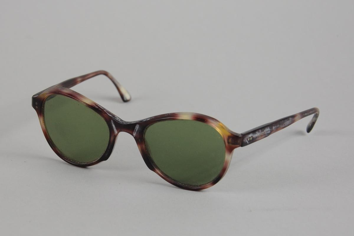 Solbriller ovale glass som er noe høyere på hver ytterside og litt lavere inn mot nesebøylen. Innfatning og stenger av plast med metallhengsler.