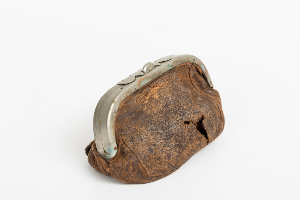Skinnpung med metallhengsle (messing?) og låseknapp. Innhold: svenske mynter 1 kroner - 7 stk. 50 ører - 13 stk. 25 ører - 13 stk. 10 ører - 44 stk. 5 ører - 16 stk.