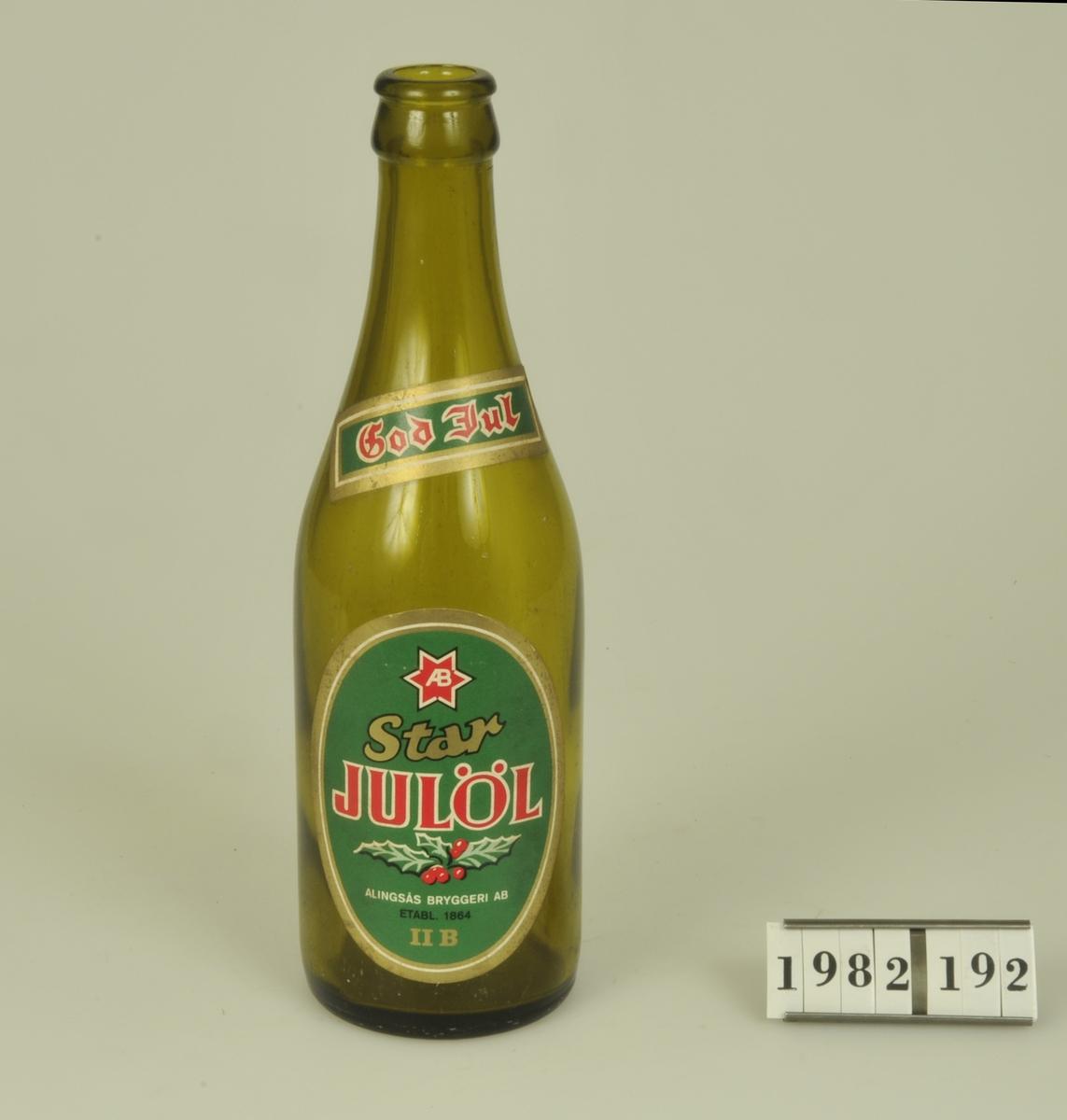 """Av brunt glas.  Etikett med grön botten och röd och guldfärgad text - """"Star Julöl Alingsås Bryggeri AB. Etabl. 1864 II B""""."""
