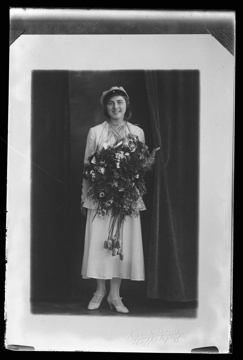 """Porträtt av en kvinna i vita kläder, studentmössa och med blommor om halsen. I fotografens anteckningar står det """"Rep.[ro] för Hans Gustafsson""""."""