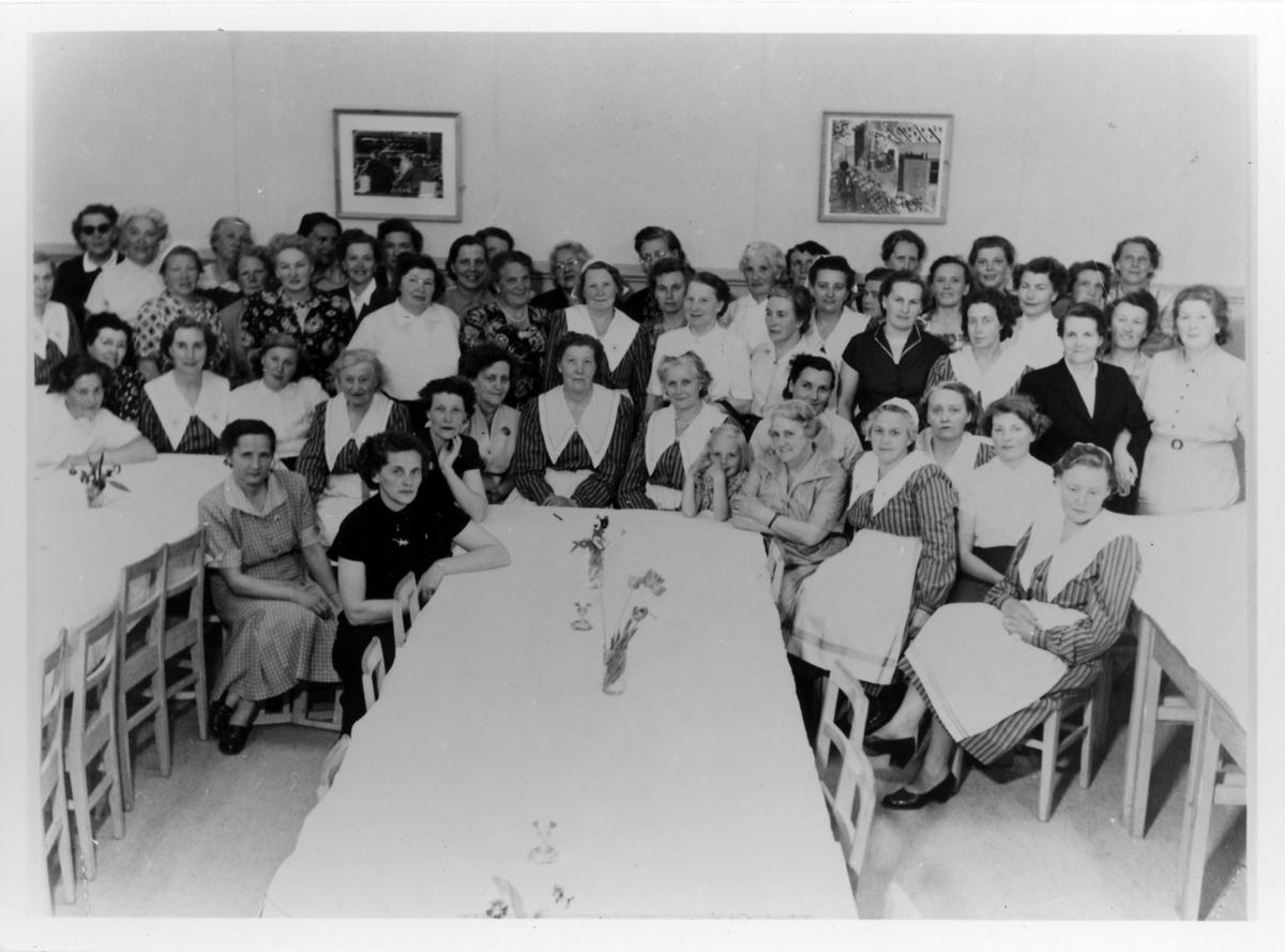 Gruppbild av omkring 60 kvinnor, stående samt sittande, från Alingsås Kooperativa Kvinnogille under deras 25-års jubileum. Vid mitten bordet ses även en flicka.