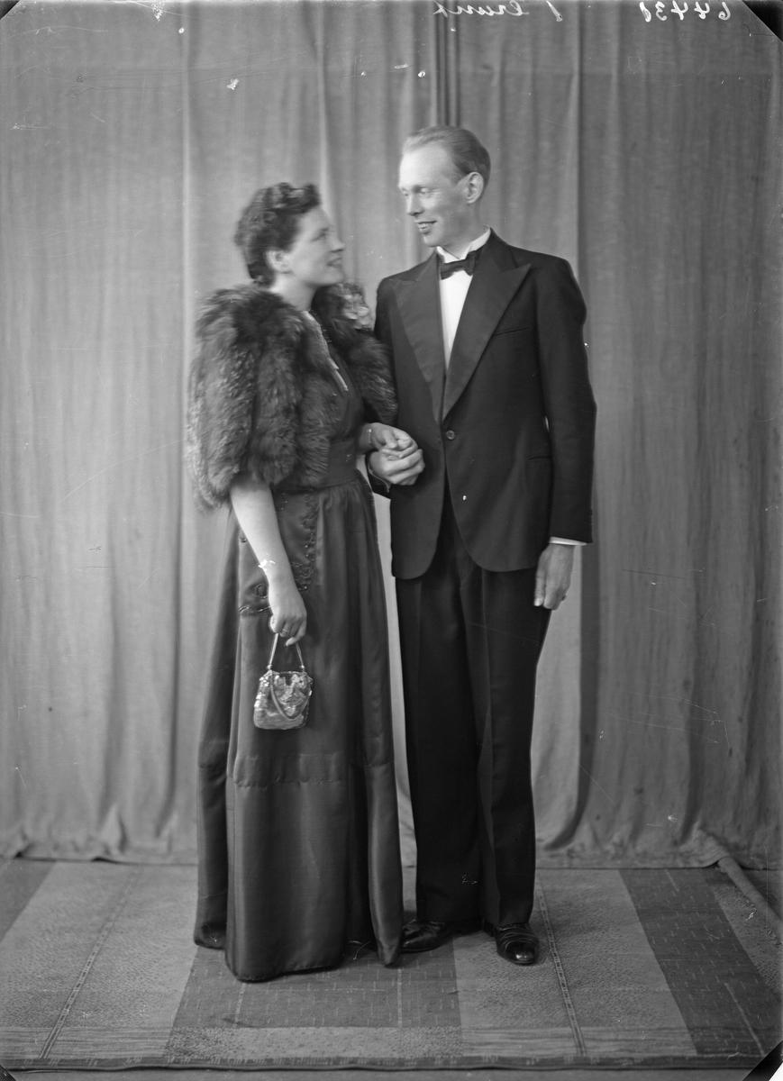 Portrett. Ung kvinne i mørk kjole og kort pelsjakke og en ung mann i smoking med mørk sløyfe. Bestilt av Bjarne N. Svendsen