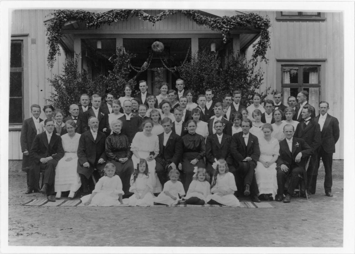 Ett femtiotal bröllopsgäster samt brudparet Nils och Elisabeth Henning utanför skolan i Ödenäs. Nils var lärare i Ödenäs från 1915 och bodde i skolan tillsammans med Elisabeth.