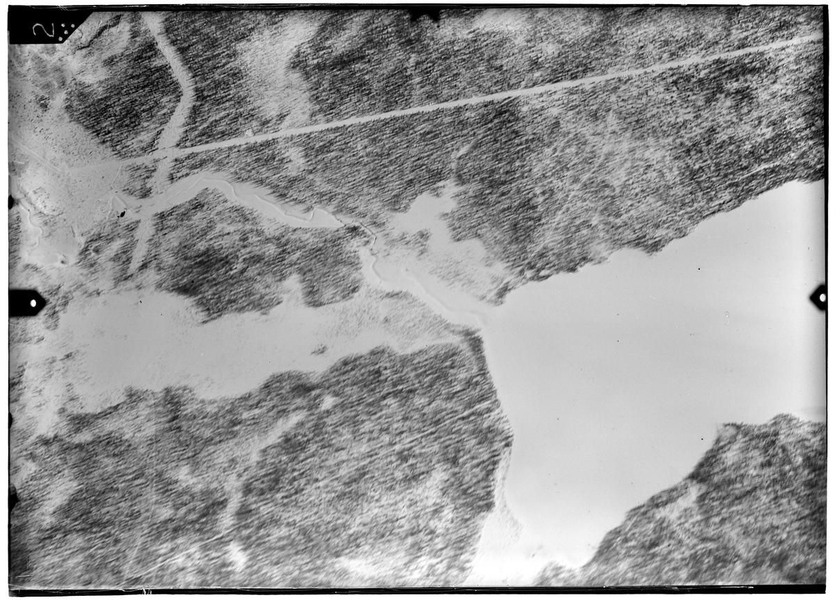 Flygfotografi av landskap kring Märkäjärvi i norra Finland under finska vinterkriget, 1940. Spaningsbild över skog, väg, å och sjö tagen av flygare vid F 19, Svenska frivilligkåren i Finland.