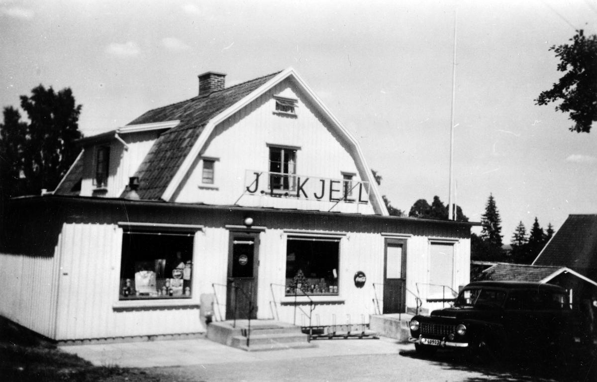 Gatuvy av J.E Kjells speceriaffär i bottenplan på en tvåplans villa. Framför affären står en bil parkerad.