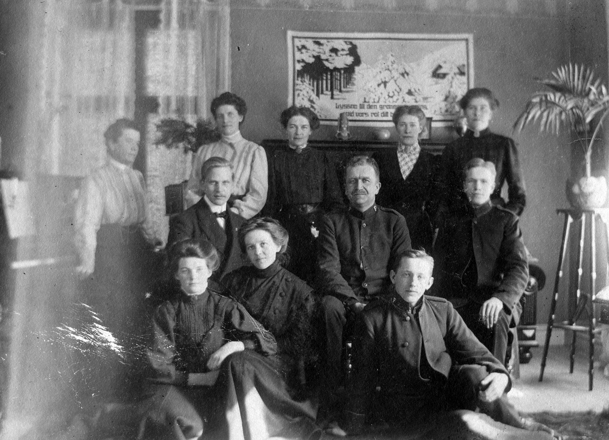 Gruppbild med delar av fräslningsarmén, 7 kvinnor och 4 män, hemma hos en av medlemmarna, Hilma Andersson, Annelund, Dammen. Bakom dom ses ett piano, ett fönster, en väggbonad och ett blomsterstativ.