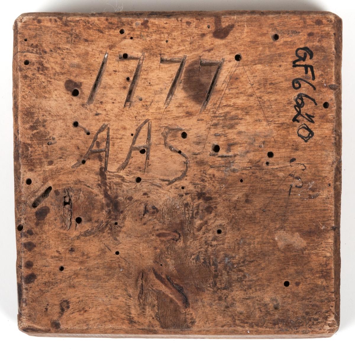 Smörstämpel märkt 1777 AAS. Skuren fyrklöver. Träet tidigare angripet av trägnagare vilket efterlämnat hål.