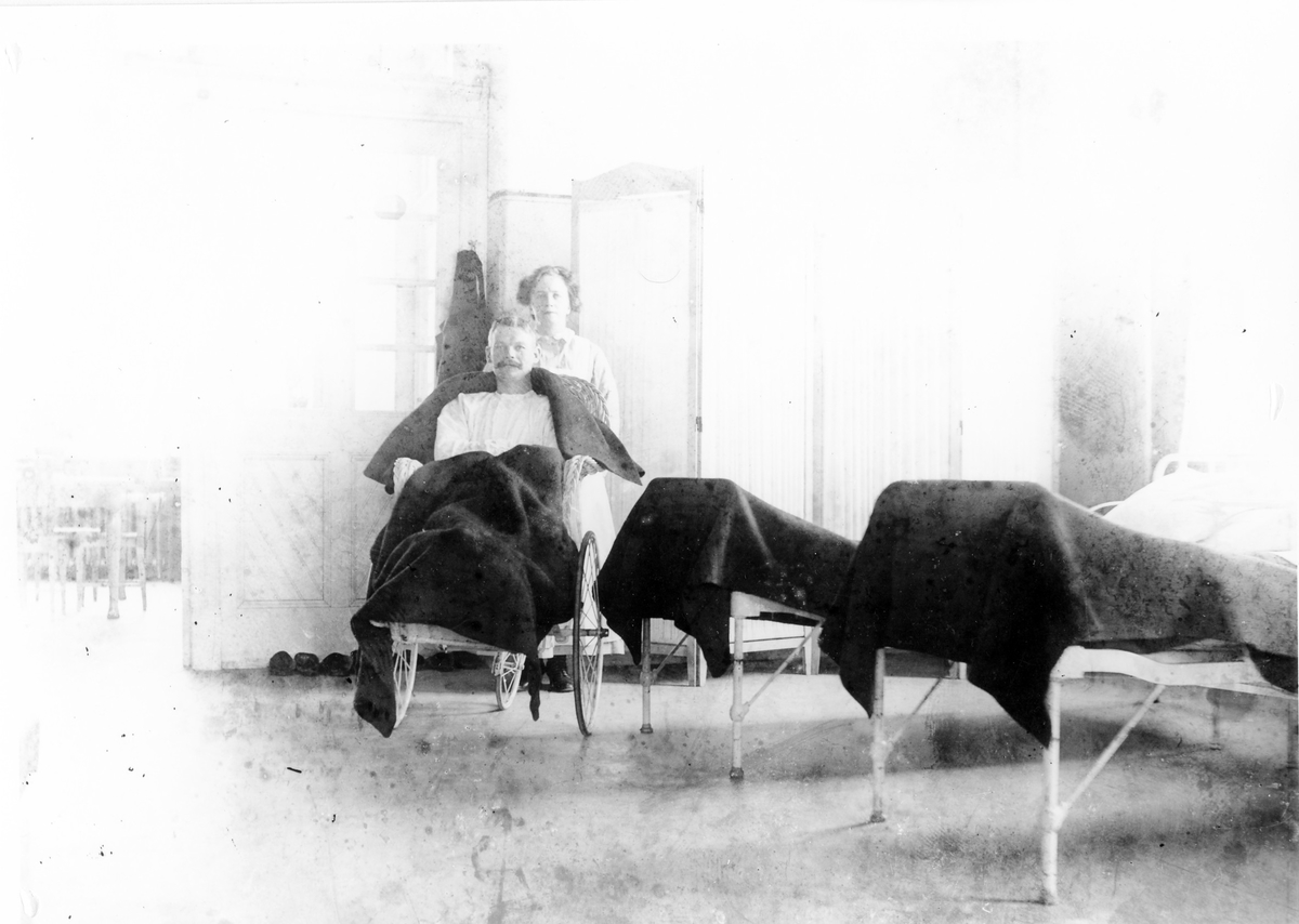 Bilden är tagen inifrån lasarettet. Till höger två sjukhussängar, en man i rullstol samt en kvinna bakom honom, troligen sjukvårdspersonal.