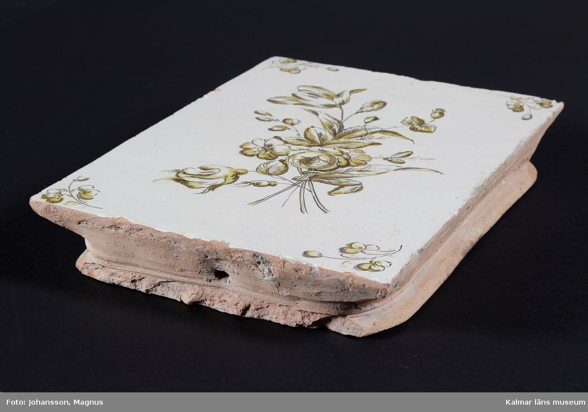 KLM 38949. Kakel. Från flera kakelugnar. Tennglasyr på gulröd lergodsskärv. Dekormålning i koboltblått, antimongult, manganlila och koppargrönt. Drejad rump.  Förteckning över samtliga kakel, med mått inom parentes, gjord i samband med inventering 1997:   :1. 1 st. fasadkakel, plant                 (31,5x23x5 cm) antimongul blomdekor :2. 1 st. fasadkakel, plant 1/2 lod     (31,5x14x5 cm) manganlila fågel och koppargrön vegetation :3. 1 st. fasadkakel, välvd                 (32,5x24,5x6 cm) färgkroppsgrön och turkos dekor :4. 4 st. simskakel plana                   (6x23x3,5 cm) blomdekor i antimongult, koppargrönt, manganlila och koboltblå     1 st. hörnsims, plant                    (6x16x3 cm) -''- :5. 27 st. blandade fragment  Kakel samlade under :6 har koboltblå dekormålning föreställande blommor, festoner, rocailler och nordstjärnor. :6. 1 st. fasadkakel, plant                  (29x22,5x6 cm) infasad för elstadslucka     1 st. hörnfasad, plant                   (30x25x10 cm)     1 st. fasadkakel, välvd                  (32,5x22x4,5 cm) med sotluckshål     1 st. nischkakel, välvd                  (27,5x20,5x4 cm)     1 st. nischkakel, välvd                  (28x23x8,5 cm)     1 st. nischkakel, välvd                  (27,5x23x8,5 cm)     1 st. nischkakel, välvd                  (28x16x8,5 cm)     1 st. fasadkakel, 1/2 lod               (31x11,5x5 cm)     1 st. fasadkakel, 1/2 lod               (25x22x6 cm) fragment     1 st. fasadkakel, 1/2 lod               (31x11,5x6 cm)     5 st. simskakel, plana                   (6x24x4 cm)     1 st. hörnsims, plan                     (5,5x16x3 cm)     4 st. fotsims, välvda                     (13x21x4,5 cm)     1 st. hörnfotsims, plan                 (12x22x7,5 cm)     45 st. blandade fragment