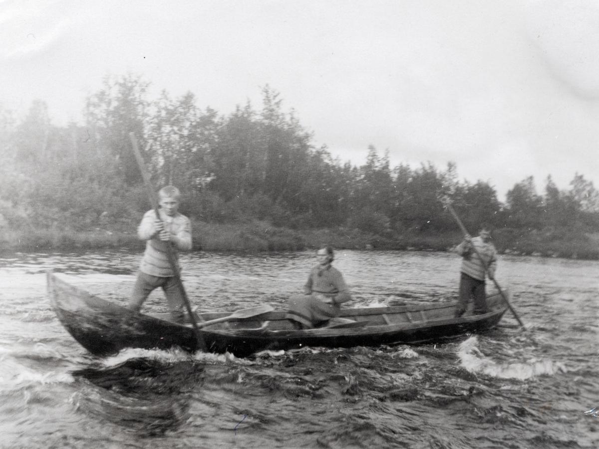 Motiv av to menn og ei kvinne i en elvebåt i Kautokeinoelva. Mennene staker mot stømmen i elva.