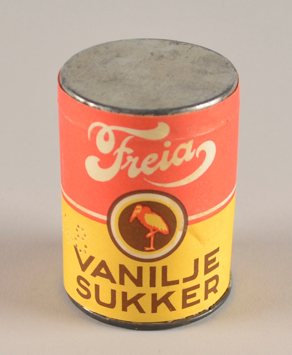 Metallboks med papir rundtmed trykk i raudt, brunt og gult. Lok oppå. Uopna. Inneheld vaniljesukker.