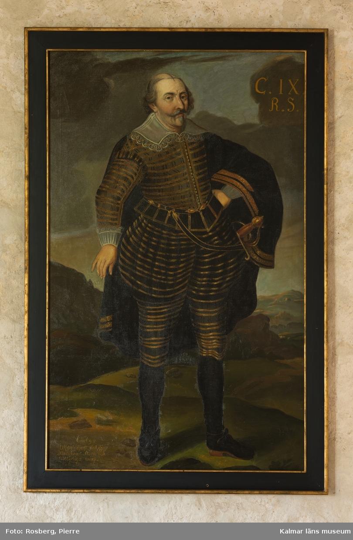 Karl IX i helfigur, stående, i mörk dräkt med guldstickningar, mantel med guldbroderier, spetskrage samt spetsar vid handlederna. Värja, svarta strumpor och skor med spännen.
