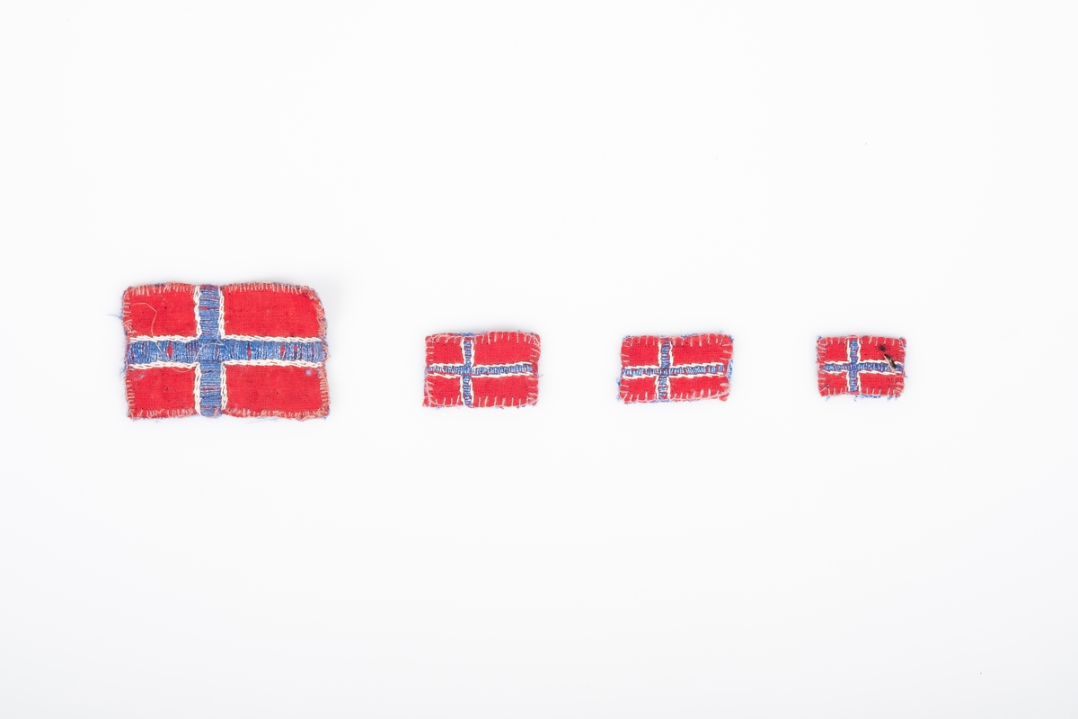 Fire små norske flagg. Flaggene er i ulike størrelser. De er sydd og brodert på hånd. De er sydd sammen av to stoffbiter, rød på forsiden og blå på baksiden. Det blå og hvite krysset på flagget er brodert.