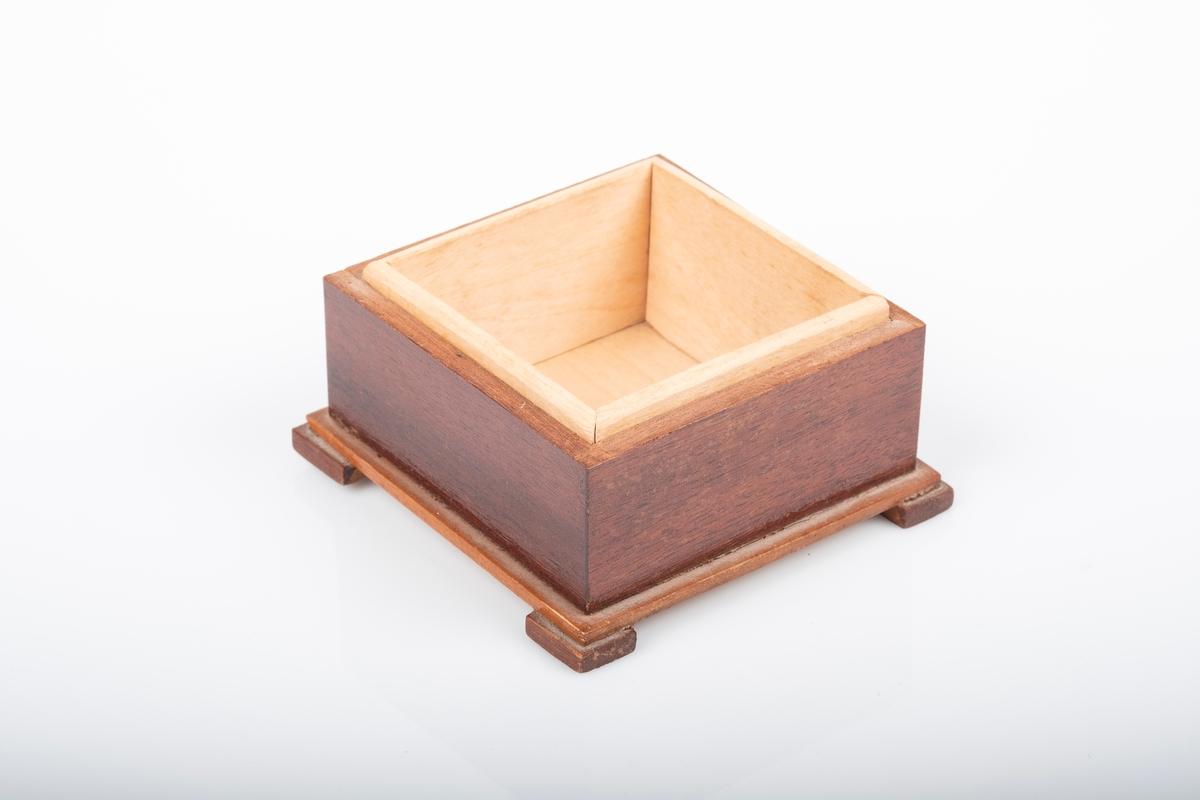 Bunn til kvadratformet, lakkert treskrin. Skrinet er laget av to treslag, ett lysere inni og ett mørkere utenpå og står på fire ben.
