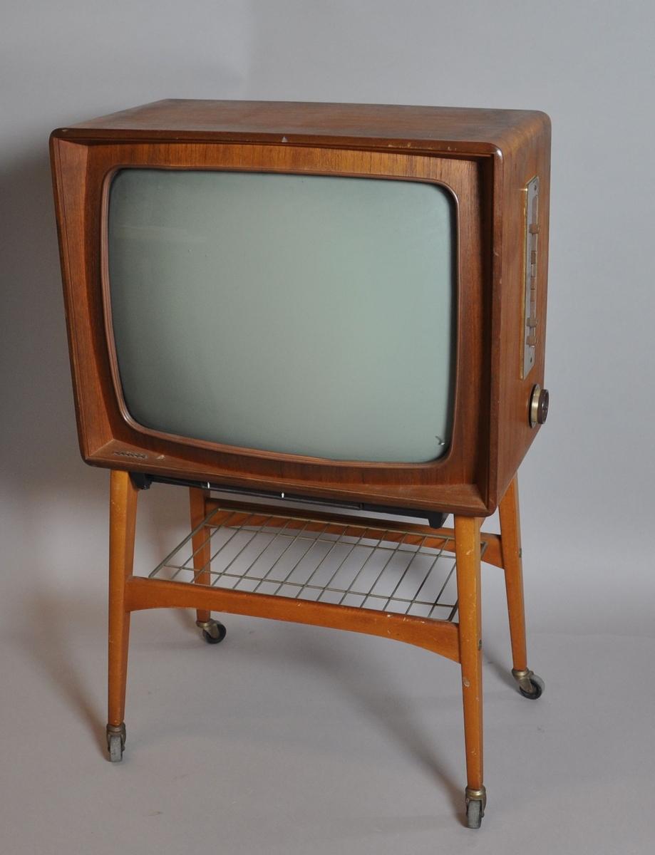 Fjernsyn med understell. Fjernsynet har kabinett av tre med finér, avrundede kanter. Justeringsknapper på høyre side, én knapp mangler. Stativet har fire bein med hjul og rist av metall festet i sprosser mellom beinene. På baksiden er det et hull i plastdekselet.