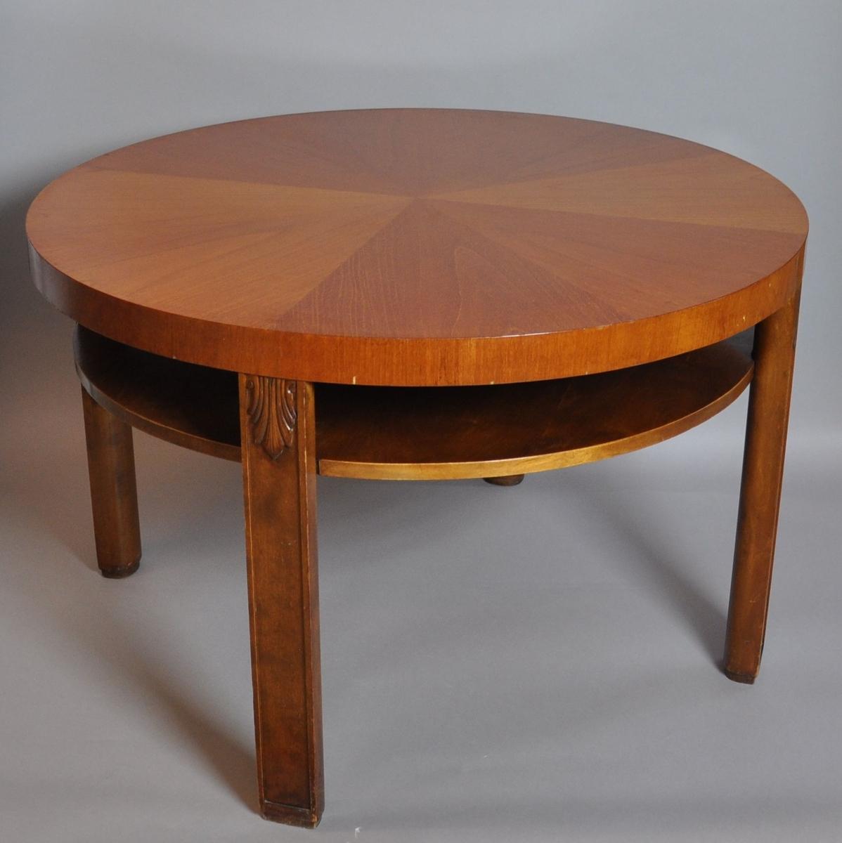 Rundt bord av tre. Bordet står på fire rektangulære bein med treskåret palmett øverst, og dekorativ innfelling i treverket. Det er en rund hylle under bordplaten.