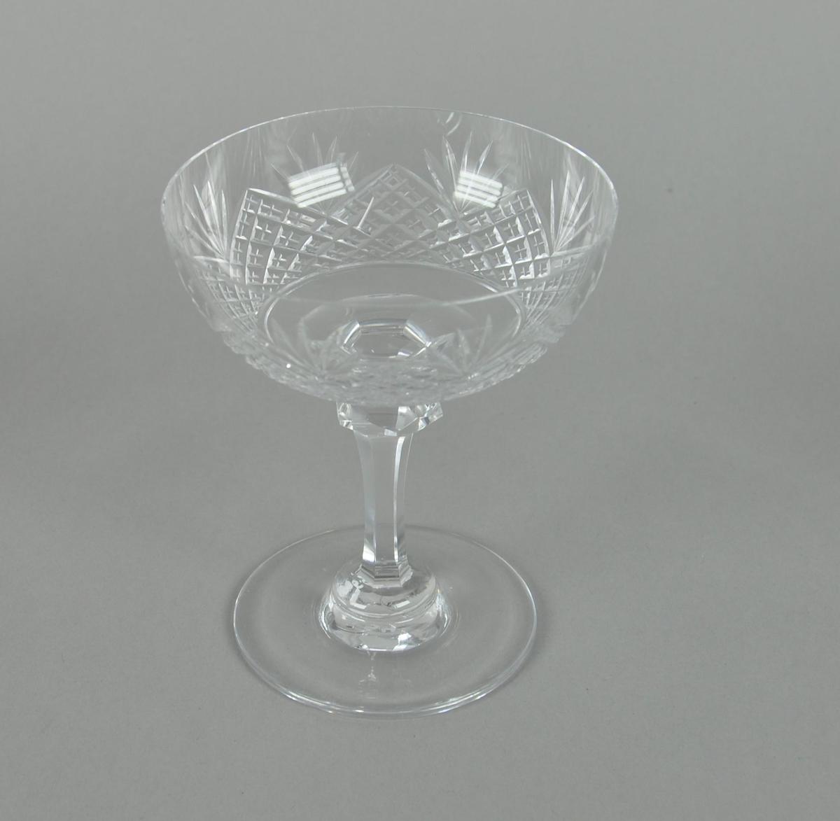 Sjampanjeglass av krystall. Glasset har rund form med sekskantet stett og rund sokkel. På utsiden av glasset er det innrisset dekor av kryssmønstre og palmetter.