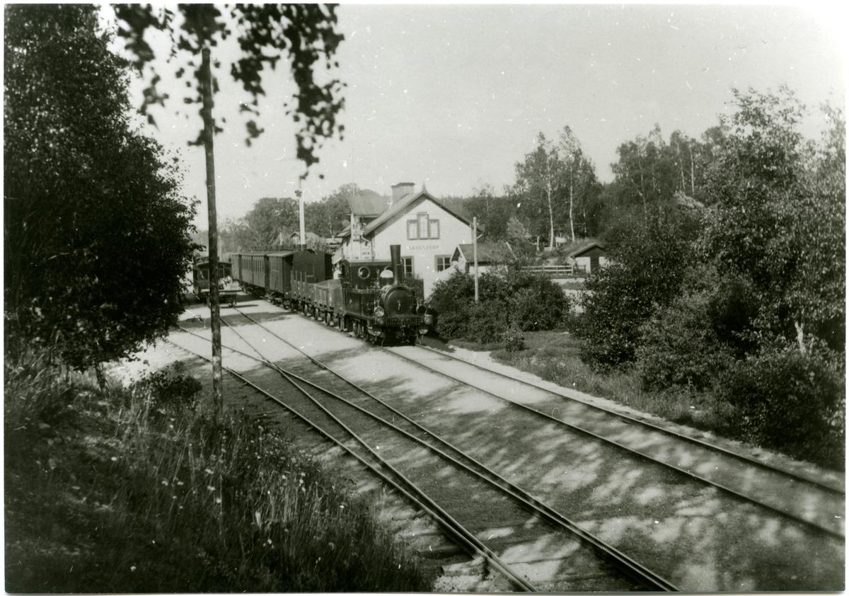 Text på bilden - Skogstorp station med OFWJ - tåg.   OFWJ är förkortning för Oxelösund - Flen - Västmanlands Järnväg.