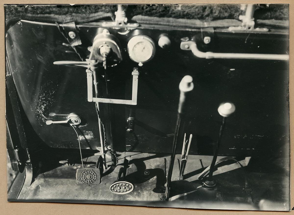 Motordressin förarplats. Gas och broms pedal, samt handbroms, växelspak och hastighetsmätare.