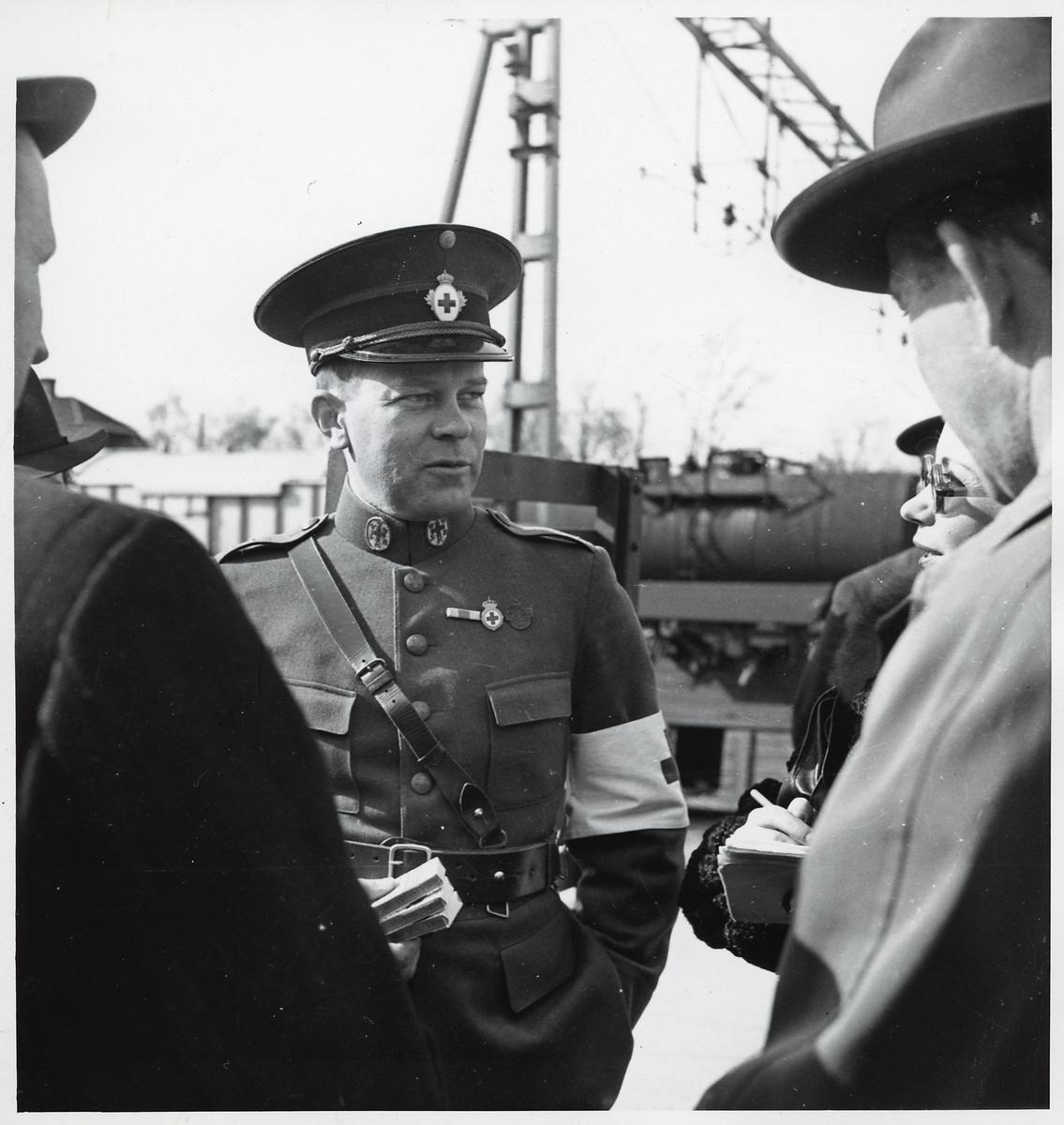 Rödakorslöjtnant Uno Rehnvall samtalar med journalister, i samband med att ett tyskt sjukvårdståg är på Hallsbergs station under Andra Världskriget.